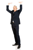 Full length businessman pushing invisible ceiling Stock Photo