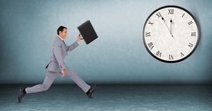 Full length of businessman running late with clock in background royalty free stock images