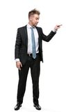 Full length of businessman setting against something. Full-length portrait of business man pushing something who wears suit with blue tie, isolated on white royalty free stock photography