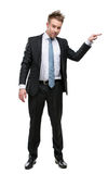 Full length of businessman shoving something. Full-length portrait of business man resting against something who wears suit with blue tie, isolated on white royalty free stock photos