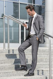 Full length of businessman text messaging through cell phone while standing on steps outside office Royalty Free Stock Photography