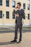 Full length of businessman using cell phone against office building Royalty Free Stock Photos