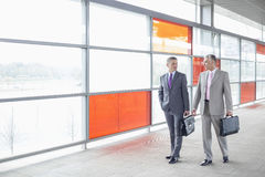 Full length of businessmen with briefcase walking in railroad station Stock Photo