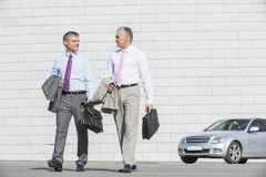 Full length of businessmen with briefcases walking on street Stock Images