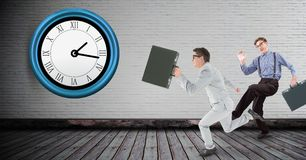 Full length of businessmen running late with clock on wall Stock Photography