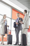 Full length of businesspeople with coffee cups talking on railroad platform Royalty Free Stock Photos