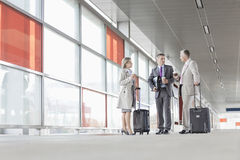 Full length of businesspeople with luggage talking on railroad platform royalty free stock photography