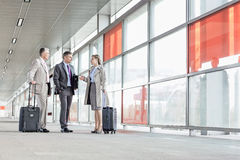 Full length of businesspeople with luggage talking on railroad platform Royalty Free Stock Photo