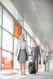 Full length of businesspeople with luggage walking in railroad station Stock Photo