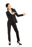 Full length businesswoman pointing to the right Stock Photo