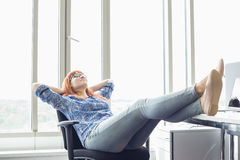 Full-length of businesswoman relaxing with feet up at desk in creative office Royalty Free Stock Photography