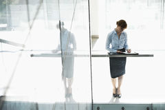 Full-length of businesswoman writing on document in office stock photography