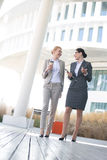 Full-length of businesswomen conversing outside office building Royalty Free Stock Images