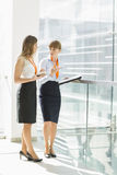 Full-length of businesswomen discussing over tablet PC while standing by railing in office Royalty Free Stock Photos