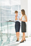Full-length of businesswomen discussing over tablet PC while standing by railing in office Royalty Free Stock Images