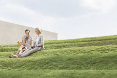 Full length of businesswomen with disposable coffee cup and laptop sitting on grass steps against sky Stock Photo