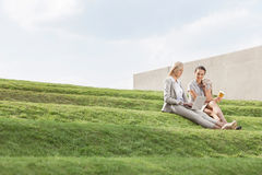 Full length of businesswomen with disposable coffee cup and laptop sitting on grass steps against sky Royalty Free Stock Image