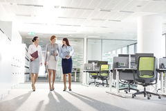 Full-length of businesswomen with file folders walking in office Stock Images