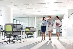 Full-length of businesswomen with file folders walking in office stock photo