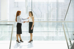 Full-length of businesswomen shaking hands at office hallway stock photography
