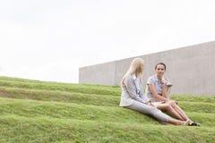 Full length of businesswomen sitting on grass steps against sky Stock Images