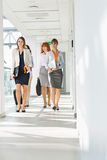 Full-length of businesswomen walking at office hallway royalty free stock image