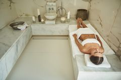 Full length of calm lady lying on the towel in Turkish bath stock images
