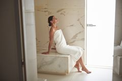 Full length of calm woman relaxing in Turkish bath and smiling stock image