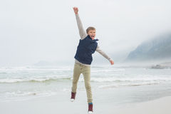Full length of a casual boy jumping at beach Royalty Free Stock Image