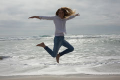 Full length of a casual woman jumping at beach Royalty Free Stock Photos