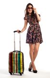 Full length of casual woman standing with travel suitcase. Isolated on white background Stock Images