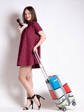 Full length of casual woman standing with travel suitcase - isolated on white background Royalty Free Stock Images