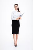 Full length of cheerful business woman standing and holding clipboard Stock Images