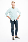 Full length of cheerful handsome young man standing and smiling. Full length of cheerful handsome young man in shirt and jeans standing and smiling over white royalty free stock photos