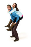 Full length of cheerful man carrying girlfriend on back Stock Images