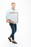 Full length of cheerful young man walking and holding whiteboard Royalty Free Stock Photos