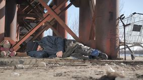 Cold homeless beggar sleeping under bridge. Full length cold homeless beggar male in jacket sleeping under the bridge in fall, eyes covered with hat. Urban stock footage