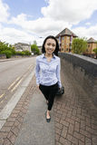 Full length of confident asian businesswoman with luggage walking on sidewalk Stock Photo