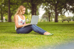 Full length of confident woman using laptop at park Stock Image