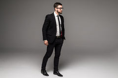 Full length of confident young businessmen in sunglasses standing isolated on grey Stock Photos