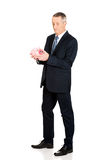 Full length confused businessman holding piggybank Royalty Free Stock Photos