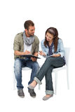 Full length of a cool couple writing in notepads Royalty Free Stock Images