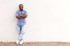 Full length cool young african man leaning against white wall and smiling Royalty Free Stock Photos