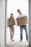 Full-length of couple with cardboard boxes standing in front of entrance stock image