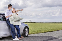 Full length of couple with map discussing direction while leaning on car at countryside Stock Photos