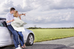 Full length of couple with map discussing direction while leaning on car at countryside Stock Image