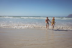 Full length of couple running on shore at beach Stock Images