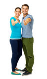 Full Length Of Couple Showing Thumbs Up Sign. Full length portrait of happy couple showing thumbs up sign over white background. Vertical shot Royalty Free Stock Photo