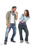Full length of a couple singing into microphones Stock Photography