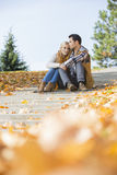 Full length of couple sitting on steps in park Royalty Free Stock Photo